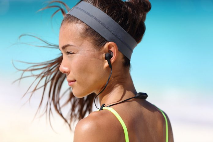 Fitness girl with sport in-ear wireless headphones. Asian female athlete woman runner wearing small Bluetooth earbuds with wing tip design for sports activities. Portrait closeup.