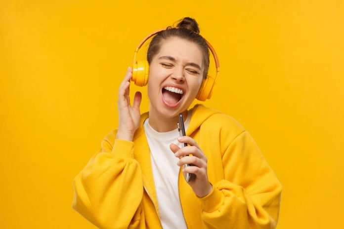 girl wearing wearing wireless headphones with a yellow background, she is smiling
