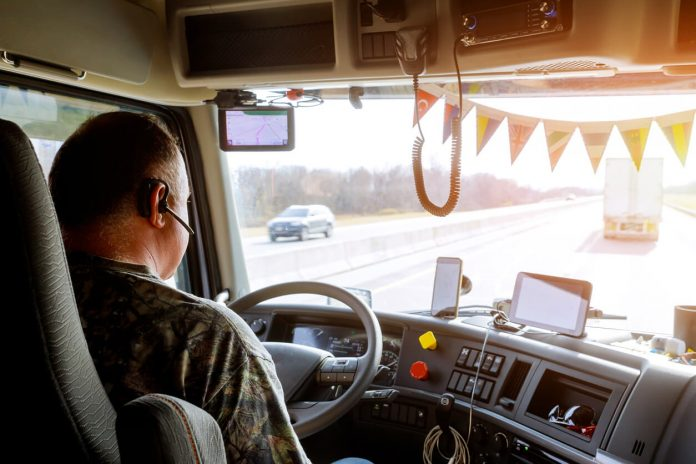 Driver in cabin of big modern truck vehicle on highway wearing headset talking to someone