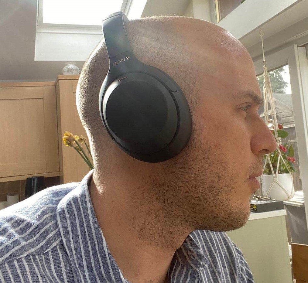 close up image of a man wearing Sony WH-1000MX4 headphones