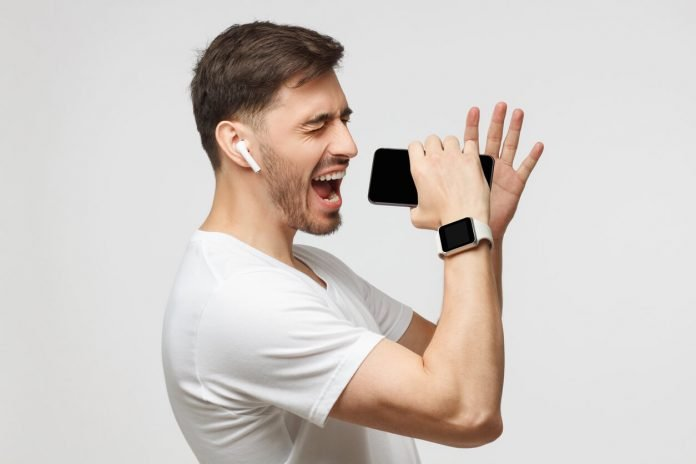 Young handsome man singing his favorite song, using his phone instead microphone, wearing white t-shirt and wireless earphones