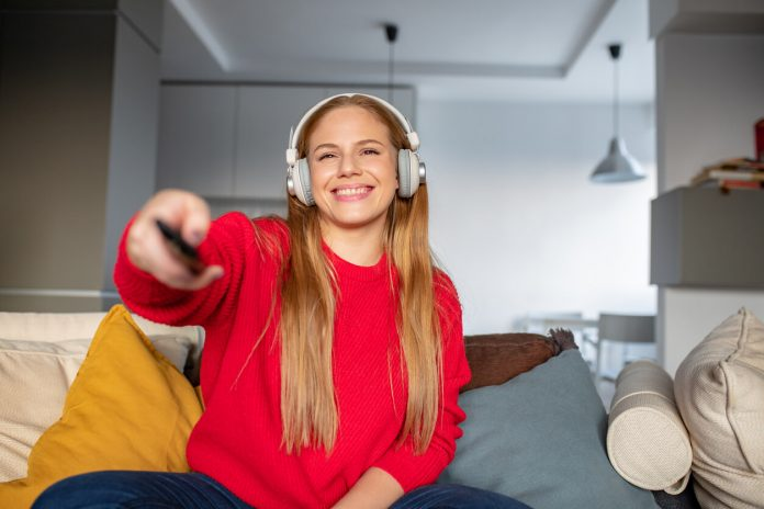 Beautiful smiling woman with headphones is watching TV and holding the remote control