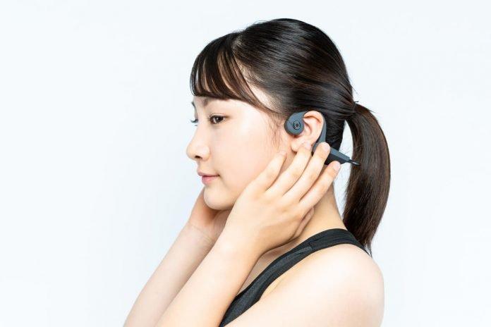 Young Asian woman wearing a bone conduction headphones.