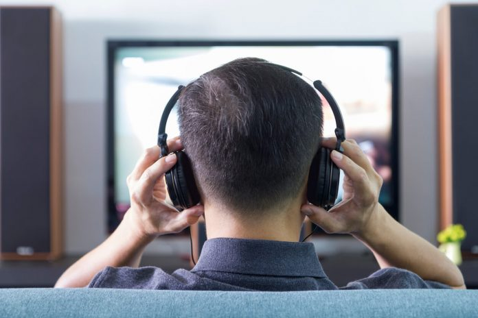 Back side of an Asian man wearing black heaphones in front of blurry out-of-focus television and home entertainment system background