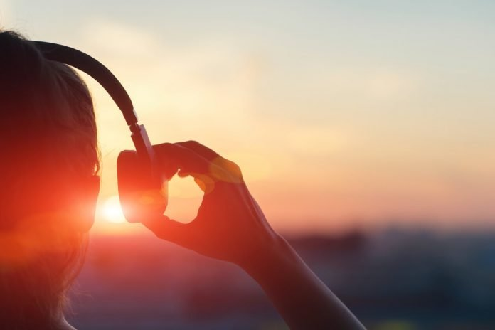 Girl lifting here right earphone on her headphones listening to music in the town at sunset