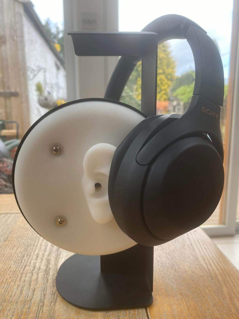 image of the Sony WH-1000XM4 headphones placed on top of a headphone testing kit